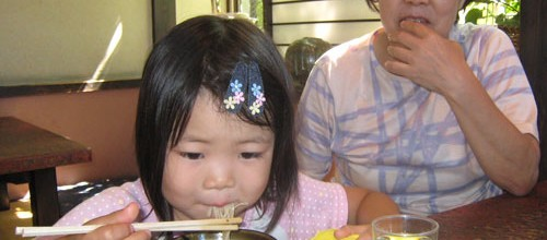 Little girl eating soba